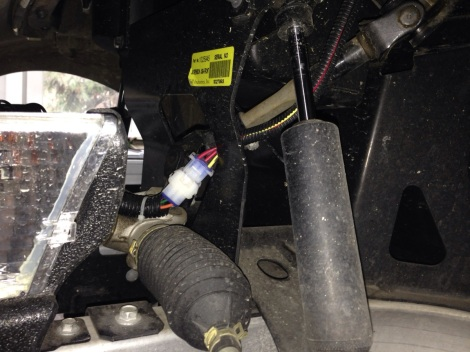 We then move onto the front of the golf cart. This particular cart was not one that SC Carts built, here you can see the headlight wiring harness is ran down beside the steering shaft. When we turn the steering shaft the steering knuckle clicks against the harness plug!