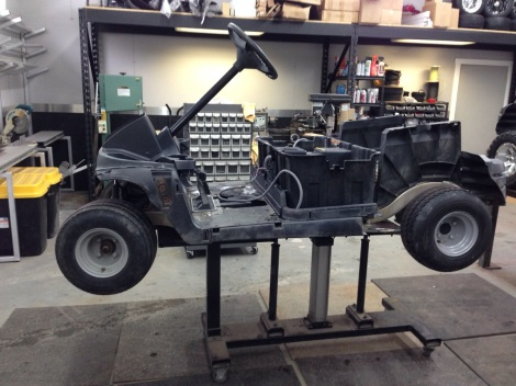 We stripped the golf cart down to a rolling chassis and then gave it a pressure wash. Next we got it settled onto our pneumatic lift table.